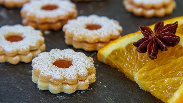spitzbugen linzer plätzchen mit marmelade und puderzucker mit zitronenscheibe in stern bzw blumenform