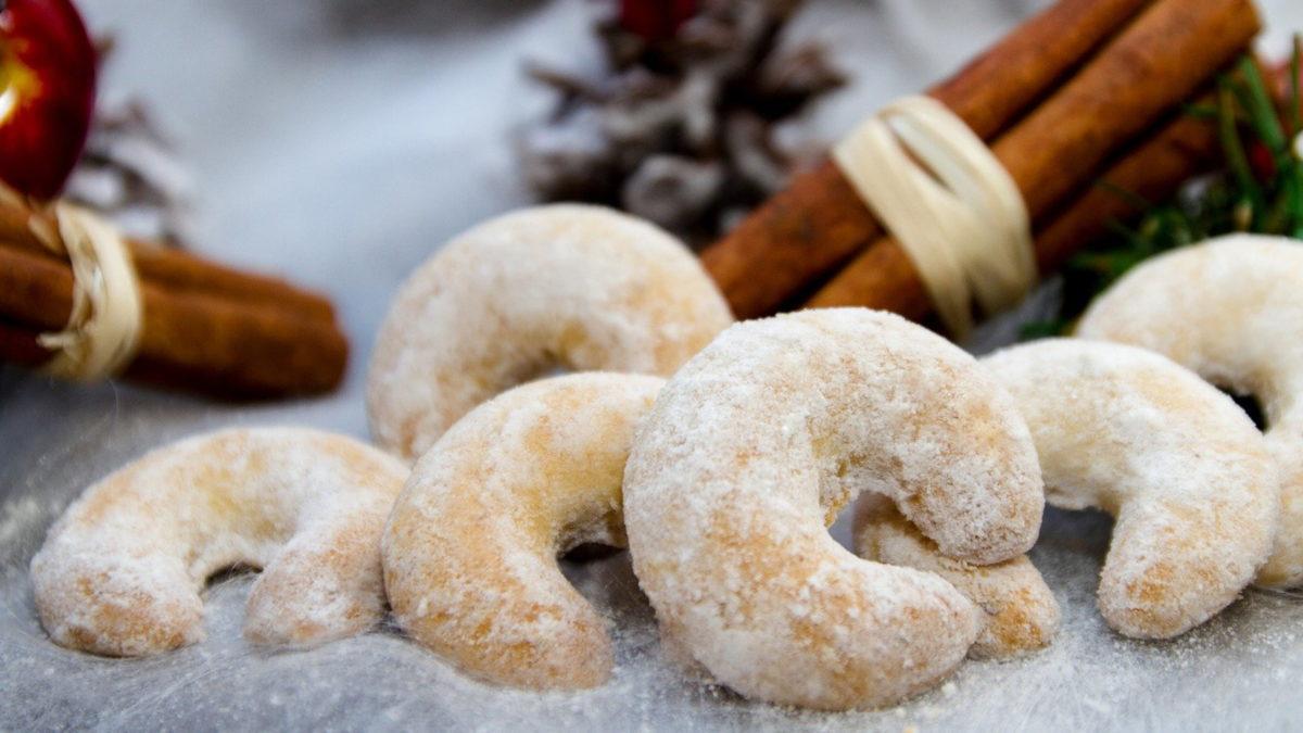 vanillekipferl mit zimtstangen und tannenzweigen als weihnachtliche dekoration