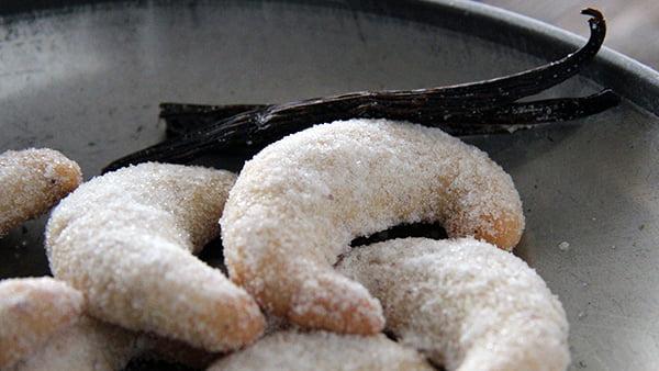 Vanillekipferl mit Puderzucker und Vanilleschote auf Metallteller