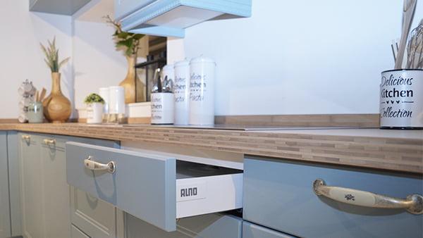 blaue landhausküche von alno bei küchen staude mit holz arbeitsplatte und verspielten griffen