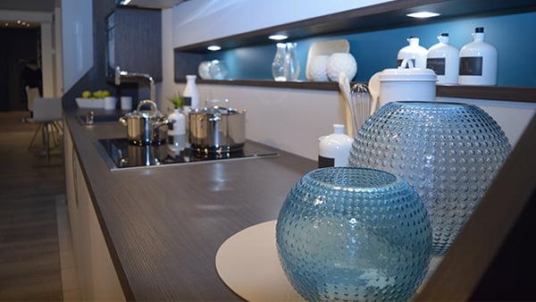 grifflose und moderne designküche von brigitte küchen im detail mit blauen glasvasen und licht im regal