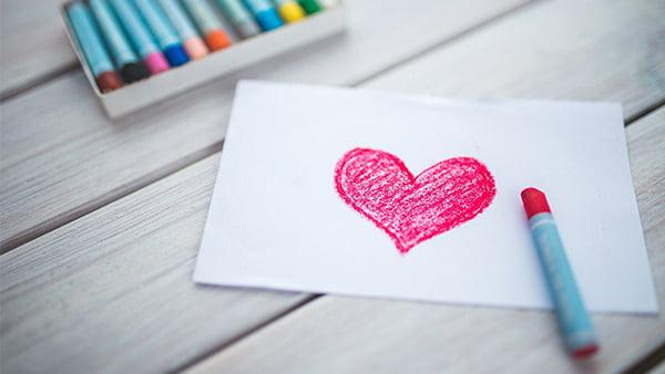 selbstgemaltes Herz mit kinderbuntmalstift in rot auf weißem Blatt Papier im Querformat