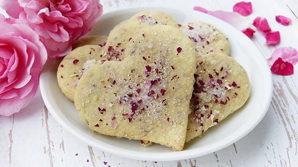 Herzkekse mit rosenblättern und zucker bestreut auf einem kleinen weißen teller mit rosen als deko drumherum