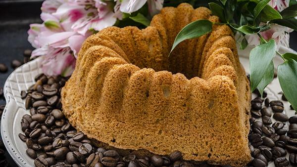 Gugelhupfkuchen in Herzform angerichtet auf einem Teller mit Kaffeebohnen