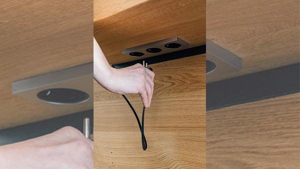 versteckte steckdosenleiste unterhalb einer holzarbeitsplatte
