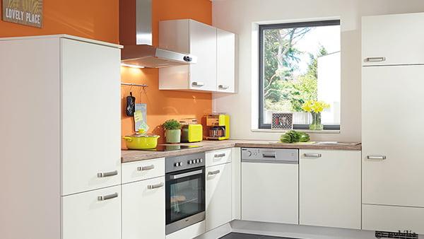 Klassische Nobilia Küche in weiß mit silbernen Griffen vor orangefarbener Wand