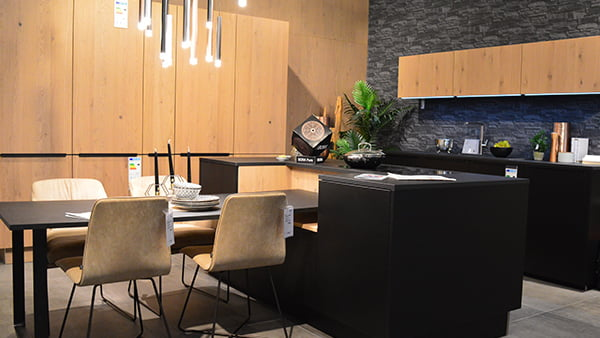 Moderne interlivinig küche in schwarz mit geschlossenen holzregalen und integriertem esstisch mit vier grauen stühlen