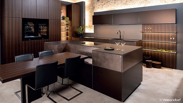elegante warendorf küche aus dunklem holz mit edlen lichtelementen und kücheninsel mit integriertem holztisch sowie vier schwarzen stühlen