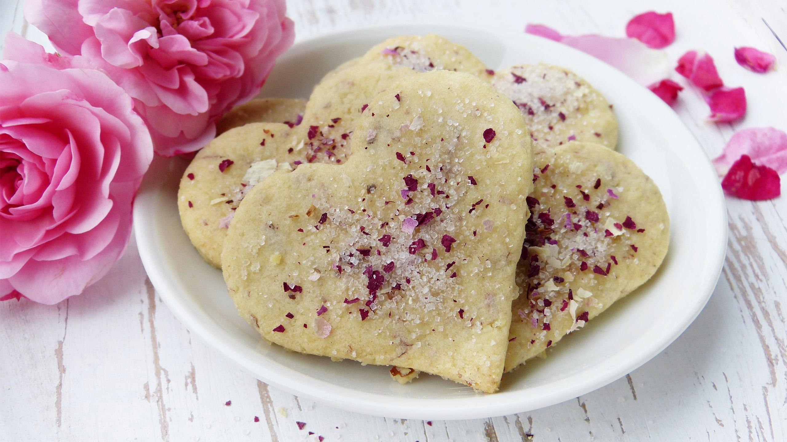 herzkekse zum valentinstag mit zucker und rosenblättern bestreut