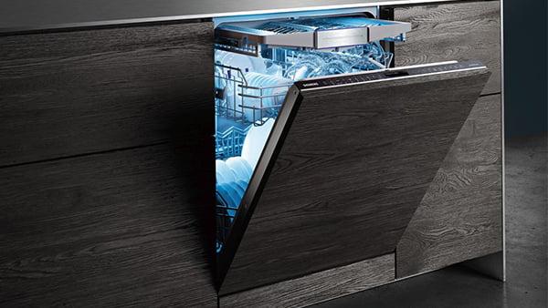 geöffneter einbaugeschirrspüler mit blauem licht im innenraum hinter betonoptik
