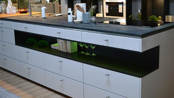 grüne lichtleiste im küchenblock bei einer weißen alno küche in der küchen staude ausstellung