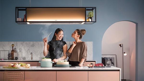 Berbel Skyline Edge mit schwarzem Rahmen und Ablagefläche in einer rosa Küche mit zwei Frauen am Kochen