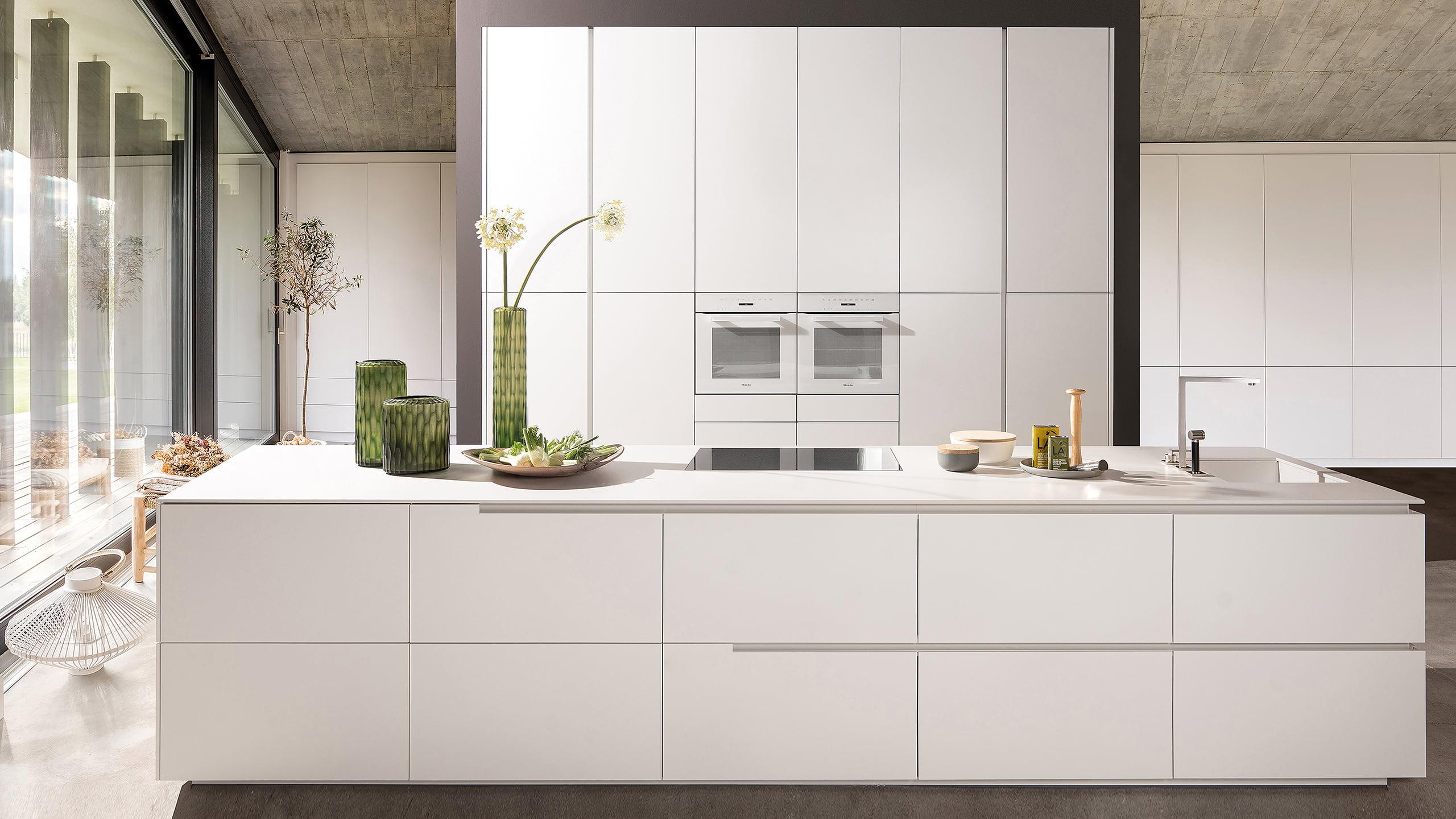 elegante weiße küche ohne griffe von warendorf mit küchenhochschrank und kochinsel