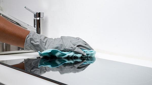 reinigung eines glaskeramik kochfelds mit blauem lappen und handschuh