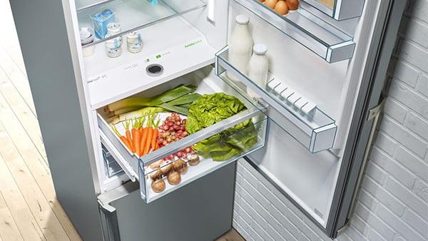 detailaufnahme einer kühl-gefrier-kombination mit geöffneter kühlschranktür und gemüsefach