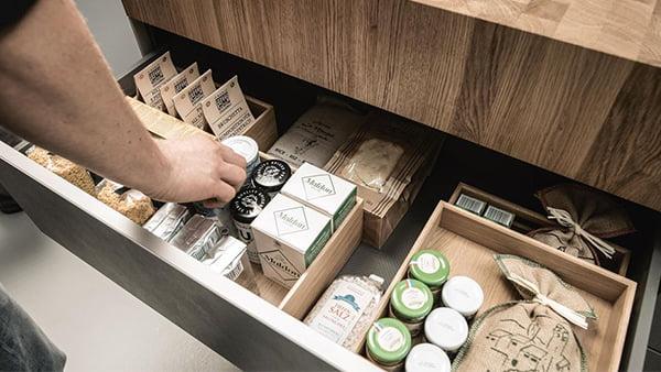 geöffnete schublade mit kochutensilien und holzboxen als symbolbild für clevere schubladeneinsätze