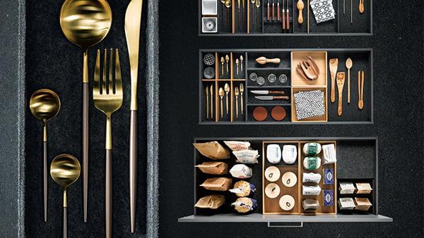 dunkle besteckeinsätze und schubladeneinsätze mit goldenem geschirr und kochutensilien