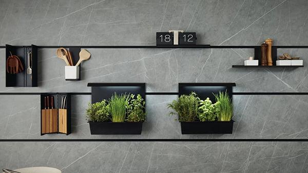 schwarzes next125 cube paneelsystem an grauer beton rückpaneel mit zubehör aus kräutergarten und messerblock