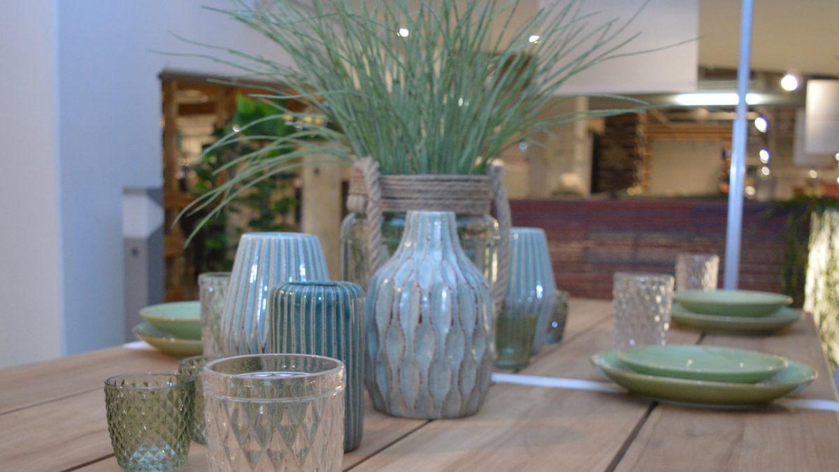 tischdeko für garten und esstich im frühling mit blau grünen vasen und tellern